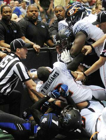 Officials attempt to break up a fight between the San Antonio Talons and the Spokane Shock, in the white uniforms, during AFL action in the Alamodome on Saturday, March 17, 2012.  Billy Calzada / San Antonio Express-News Photo: Billy Calzada, Express-News / San Antonio Express-News
