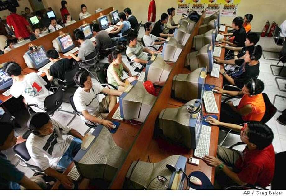Chinese youths crowd an internet cafe in Beijing, where the government controls what they view online. Associated Press photo by Greg Baker
