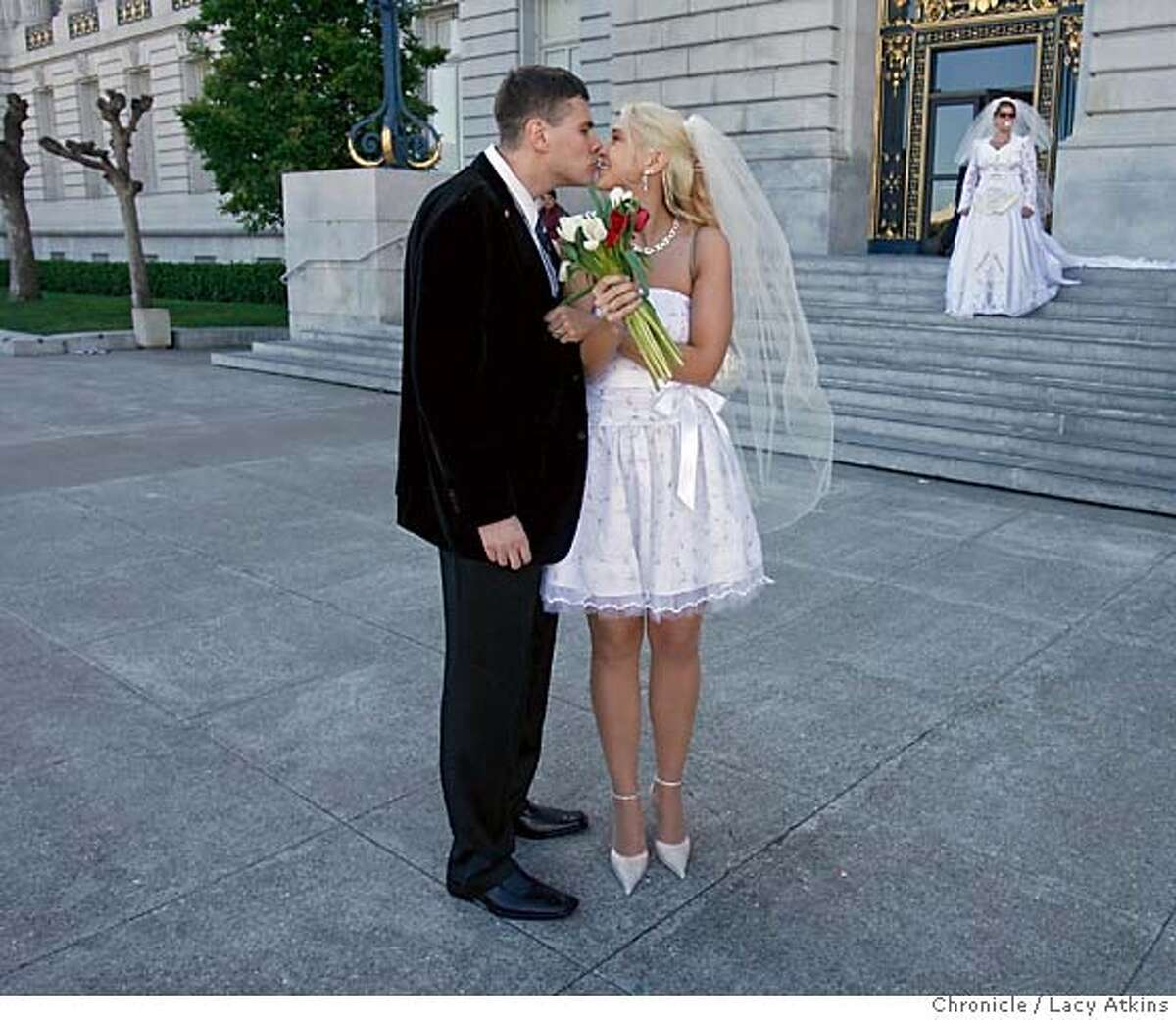"""Laurynas Misevieius and his bride Jevgenija Fedosejeva kiss after getting married at San Francisco's city Hall as Gene Segno ( in the background) with the Equality California wears tape that says, """"I DO"""" over her mouth to protest that Gay and Lesbian were being denied the right to marry on Valentines Day. couple go the City Hall in hopes to get married on Valentines Day, but were denied the right, Feb. 14, 2006, in San Francisco. Photographer:Atkins, Lacy"""
