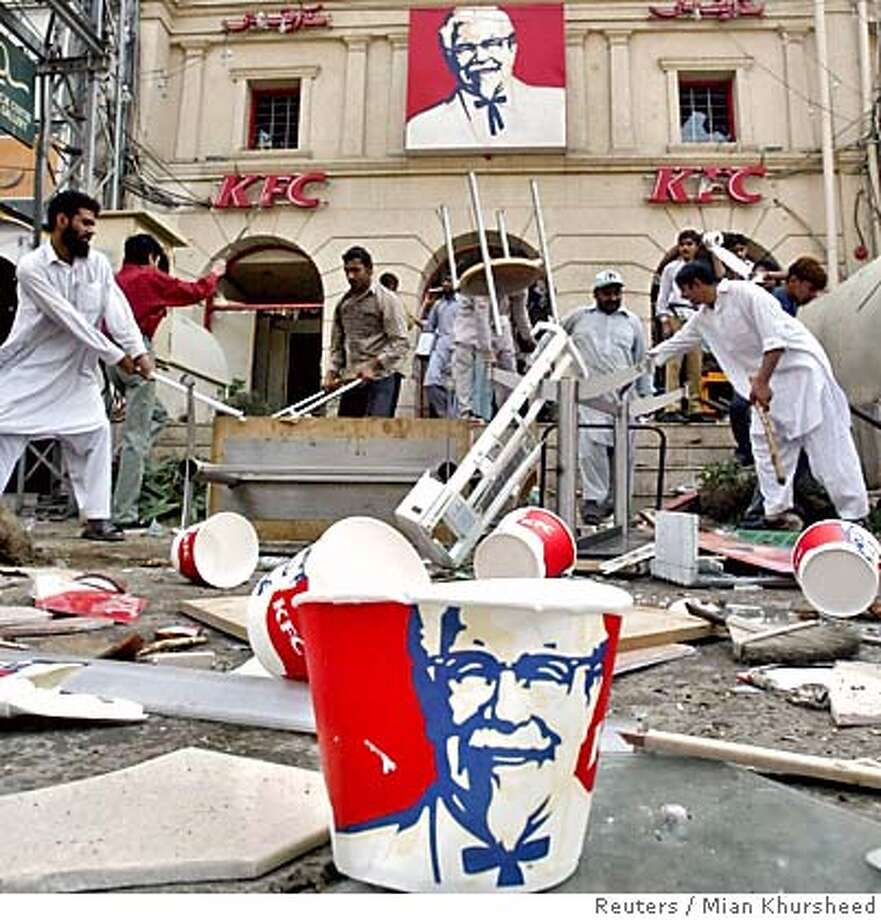 Pakistani protesters smash the items in front of KFC before setting the building on fire during a protest rally against the publication of cartoons depicting Islamic prophet Muhammad in Lahore February 14, 2006. Police used tear gas to drive out students who stormed into Islamabad's diplomatic enclave on Tuesday and protesters attacked Western businesses in Pakistan's most violent reaction yet to cartoons of the Prophet Mohammad. In the eastern city of Lahore, police fired tear gas, shot into the air and baton-charged protesters who ransacked a McDonald's franchise and set fire to outlets of KFC and Norwegian mobile phone firm Telenor, witnesses said. REUTERS/Mian KhursheedRan on: 02-15-2006  Protesters in Lahore, Pakistan, smash items in front of a KFC outlet before setting the building on fire during a protest rally against the publication of cartoons depicting the prophet Muhammad. Photo: MIAN KHURSHEED