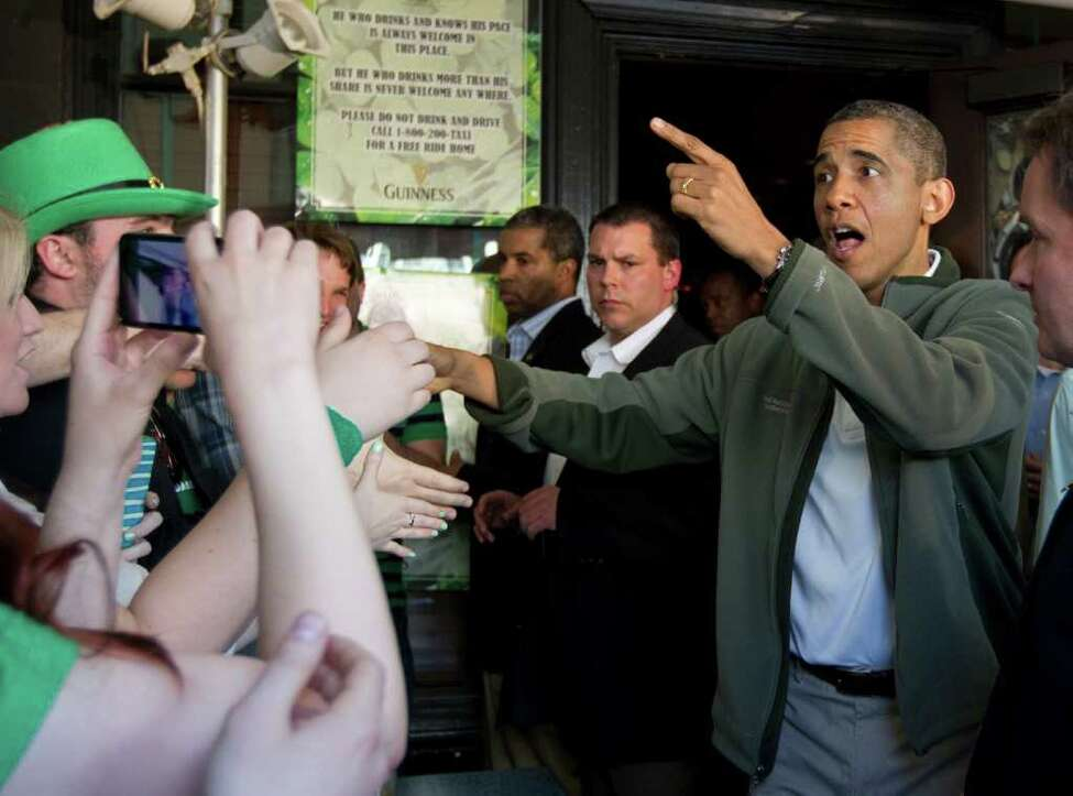 President Barack Obama greets patrons outside The Dubliner Restaurant and Pub and Restaurant on St. Patrick's Day, Saturday, March 17, 2012, in Washington. (AP Photo/Carolyn Kaster)