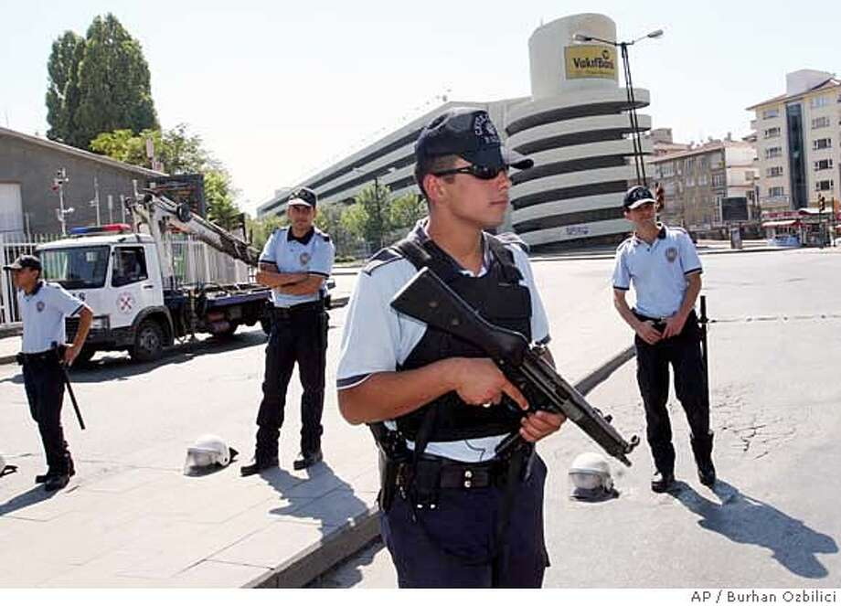 Turkish police officers stand guard outisde a security cordon surrounding a multistory carpark, seen in the background, after sniffer dogs discovered a bomb-laden vehicle parked inside, Ankara, Turkey, Tuesday, Sept. 11, 2007. Turkish authorities thwarted a potential bombing, possibly timed to coincide with the sixth anniversary of the Sept. 11 attacks, as police defused a 300-kilogram (660-pound) bomb found Tuesday on a minibus parked near an Ankara market. (AP Photo/Burhan Ozbilici) Photo: BURHAN OZBILICI