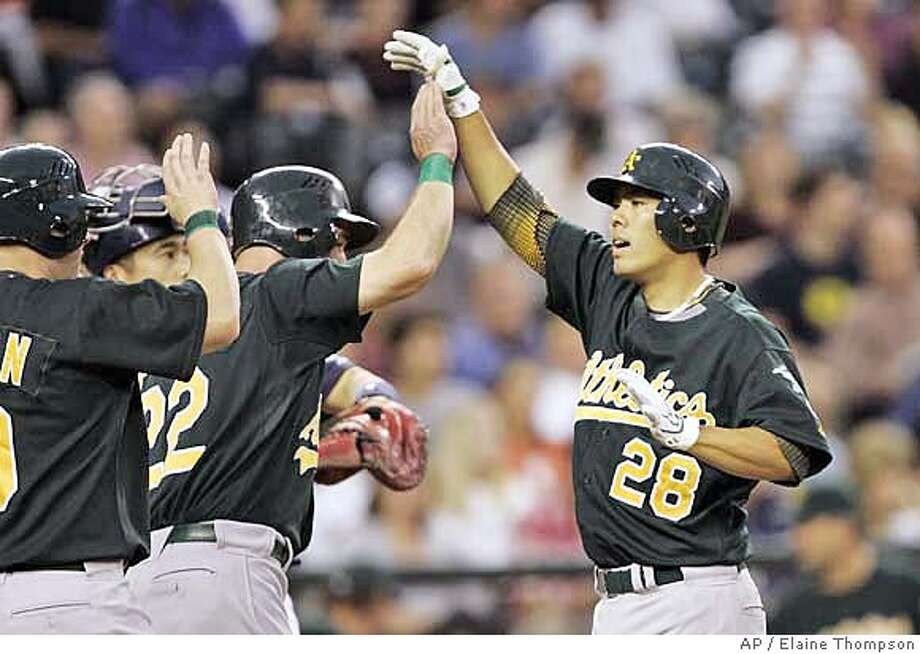 Oakland Athletics' Kurt Suzuki, right, is greeted at the plate by teammates Daric Barton, left, and Jack Hannahan after hitting a grand slam against the Seattle Mariners in the second inning during a baseball game, Monday, Sept. 10, 2007, in Seattle. (AP Photo/Elaine Thompson) Photo: Elaine Thompson