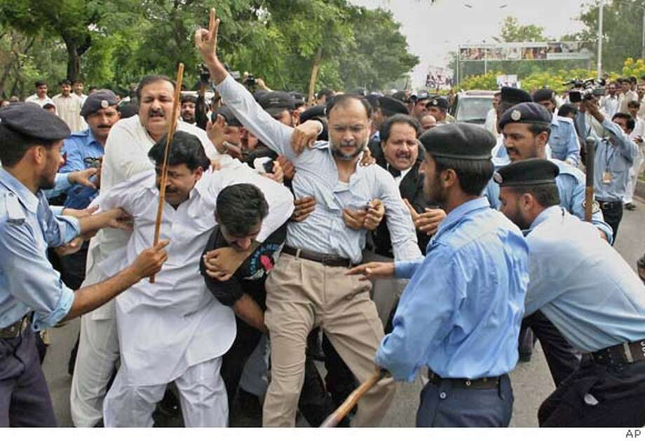 Supporters of former Pakistani Prime Minister Nawaz Sharif scuffle with police officers during a march towards the airport, Monday, Sept. 10, 2007 in Islamabad, Pakistan. Sharif was deported to Saudi Arabia, hours after he had landed in Pakistan from seven years in exile hoping to campaign against the country's U.S.-allied military ruler, officials said. (AP Photo) Photo: AP