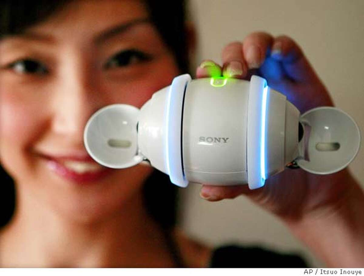 A model shows Sony Corp.'s new rolling egg-shaped digital music player swivels in Tokyo, Monday, Sept. 10, 2007. The 40,000 yen (US$354; euro258), 300 gram (11 ounce) Rolly, set to go on sale in Japan Sept. 29, comes with stereo speakers, 1 Gigabyte of internal flash memory and a battery good for about five hours of music. Overseas sales are still undecided. The smooth white gadget, small enough to sit on a palm, has sensors that recognize which way is up, allowing volume to be controlled by turning the player clockwise or counterclockwise, and tunes to be switched by pushing or pulling it on the floor. (AP Photo/Itsuo Inouye)