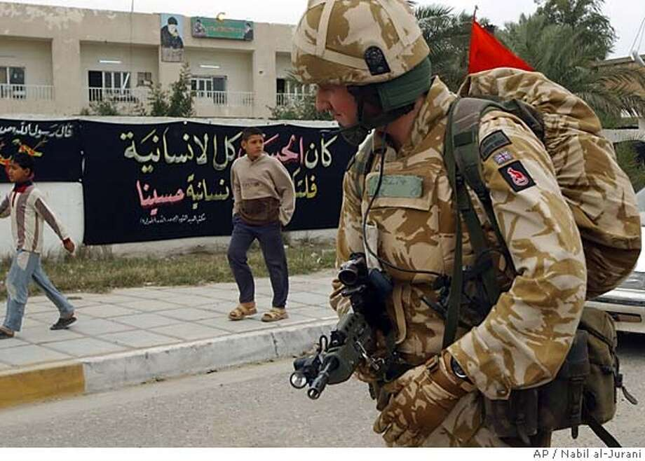 """** FILE ** A British soldier is seen patroling in Basra, Iraq's second-largest city, 550 kilometers (340 miles) southeast of Baghdad, in this Feb. 3, 2006 file photo. British television stations on Sunday screened video footage that appeared to show British troops beating Iraqi civilians. The Ministry of Defense said military police were investigating the allegations, and British Treasury chief Gordon Brown said that if the film is genuine """"this is unacceptable behavior."""" (AP Photo/Nabil al-Jurani, File) Photo: NABIL AL-JURANI"""