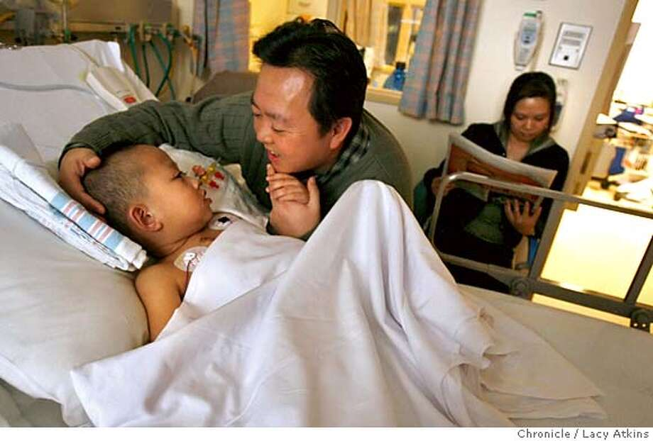 Mike Zhao holds his son Jason Zhao, five years old, hand as he sleeps in the Lucile Packard Children's Hospital, Feb. 12, 2006 in Stanford. Jason had a heart transplant after three strokes and being on the Berlin heart for 234 days, longer than anyone in North America. His mother Dongmei Zhao sits in teh background reading to paper.  Photographer:Atkins, Lacy MANDATORY CREDIT FOR PHOTOG AND SF CHRONICLE/ -MAGS OUT Photo: LACY ATKINS