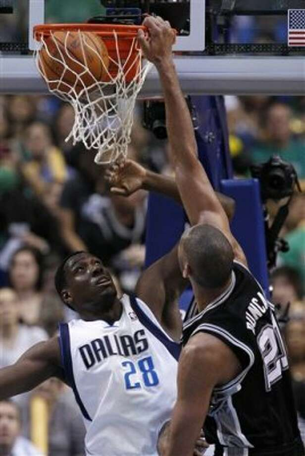 San Antonio Spurs' Tim Duncan (21) dunks over Dallas Mavericks' Ian Mahinmi (28), of France, in the first half of an NBA basketball game on Saturday, March 17, 2012, in Dallas. (AP Photo/Tony Gutierrez) (AP)