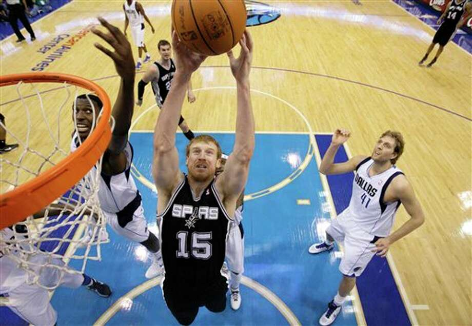 San Antonio Spurs' Matt Bonner (15) comes down with an offensive rebound over Dallas Mavericks' Ian Mahinmi, left,  of France and Dirk Nowitzki (41) of Germany in the first half of an NBA basketball game Saturday, March 17, 2012, in Dallas. (AP Photo/Tony Gutierrez) (AP)