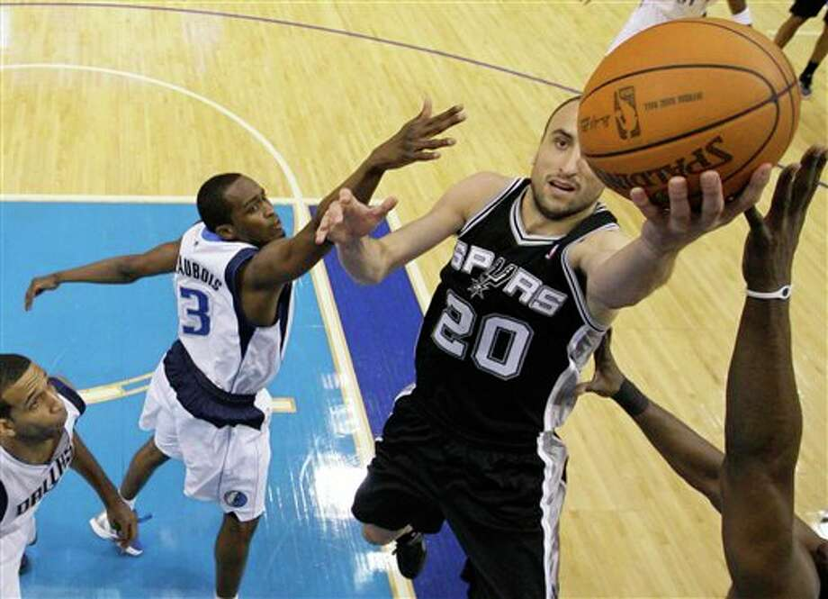 San Antonio Spurs' Manu Ginobili (20) of Argentina goes up for a shot as Dallas Mavericks' Rodrigue Beaubois (3) of Guadeloupe and Brandan Wright, bottom left, defend in the first half of an NBA basketball game Saturday, March 17, 2012, in Dallas. (AP Photo/Tony Gutierrez) (AP)