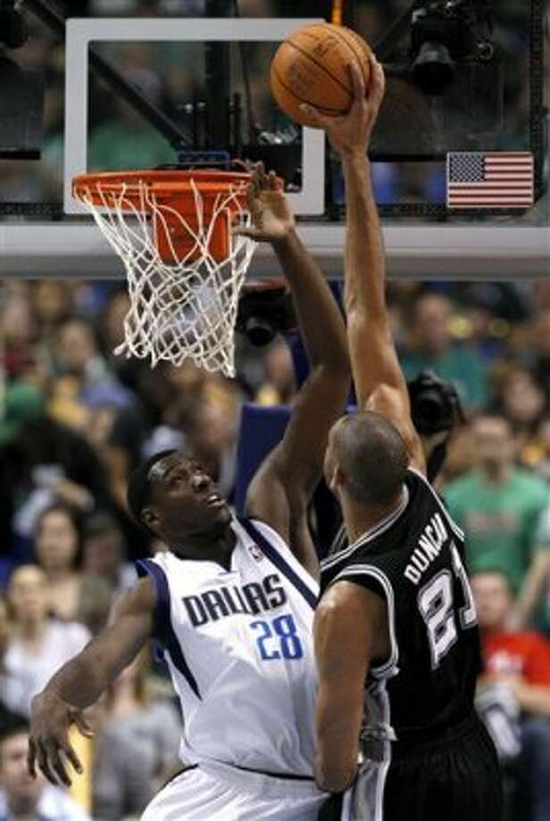 San Antonio Spurs' Tim Duncan (21) dunks over Dallas Mavericks' Ian Mahinmi (28) of France in the first half of an NBA basketball game Saturday, March 17, 2012, in Dallas. (AP Photo/Tony Gutierrez) (AP)