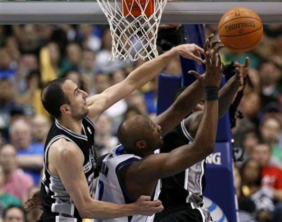San Antonio Spurs' Manu Ginobili, left, of Argentina, and Dallas Mavericks' Lamar Odom, center, compete for a rebound in the first half of an NBA basketball game on Saturday, March 17, 2012, in Dallas. (AP Photo/Tony Gutierrez) (AP)