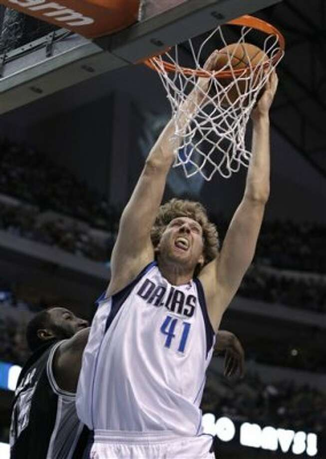 Dallas Mavericks power forward Dirk Nowitzki (41) of Germany dunks over San Antonio Spurs' DeJuan Blair, left, in the first half of an NBA basketball game Saturday, March 17, 2012, in Dallas. (AP Photo/Tony Gutierrez) (AP)