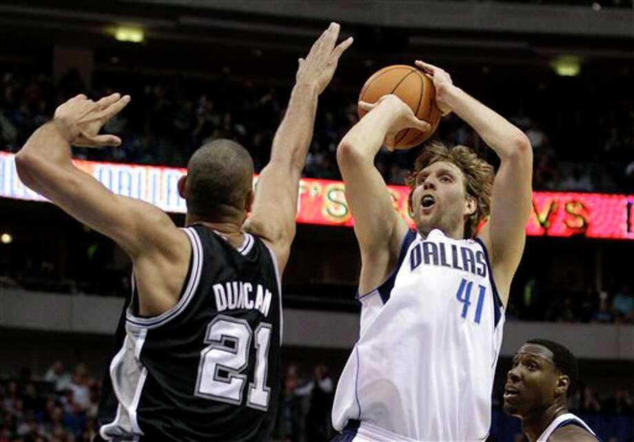 San Antonio Spurs center Tim Duncan (21) defends as Dallas Mavericks' Dirk Nowitzki (41), of Germany, attempts a shot in the first half of an NBA basketball game Saturday, March 17, 2012, in Dallas. The Mavericks' Ian Mahinmi, bottom right, of France, looks on. (AP Photo/Tony Gutierrez) (AP)