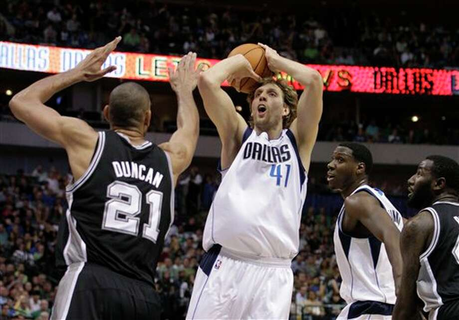 San Antonio Spurs center Tim Duncan (21) defends as Dallas Mavericks' Dirk Nowitzki (41) of Germany attempts a shot in the first half of an NBA basketball game Saturday, March 17, 2012, in Dallas. The Mavericks' Ian Mahinmi, bottom right, of France looks on. (AP Photo/Tony Gutierrez) (ASSOCIATED PRESS)