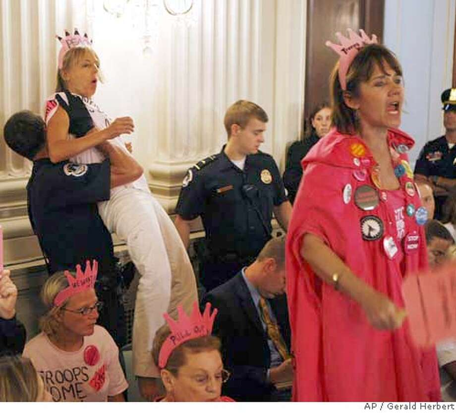 Medea Benjamin of CodePink is removed by Capitol Hill Police on Capitol Hill in Washington, Monday, Sept. 10, 2007, as Gen. David Petraeus and U.S. Ambassador to Iraq Ryan Crocker, not shown, testify on the future course of the war in Iraq before a joint hearing of the House Armed Services Committee and House Foreign Relations Committee. At right is Lydia Vickers of Tallahassee, Fl. (AP Photo/Gerald Herbert) Photo: Gerald Herbert