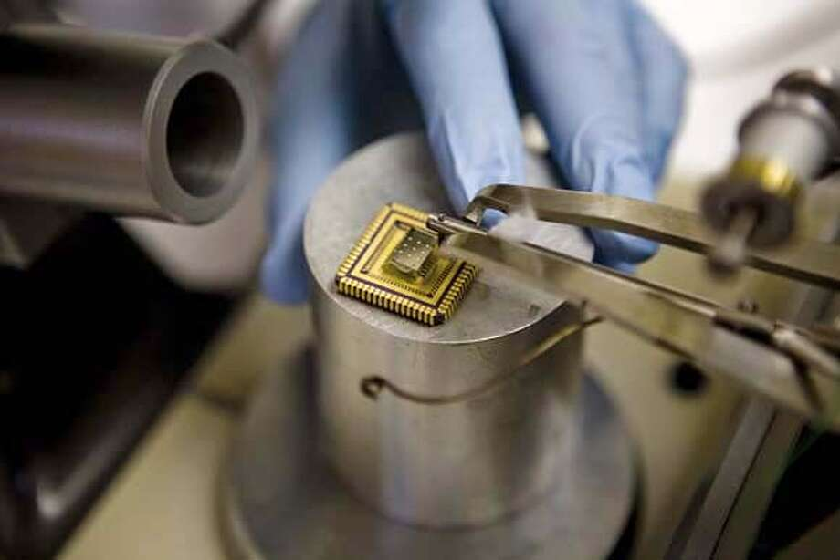 The prototype skin patch reveals the intricate components involved in this industry-first drug delivery system. The sparkling dots on the top of the black square platform are the micro-needles, and the very small off-white bottles underneath are the reservoirs where the medicine is held. The gold square is the microprocessor that controls dosage timing, size and history. Photo: Ho