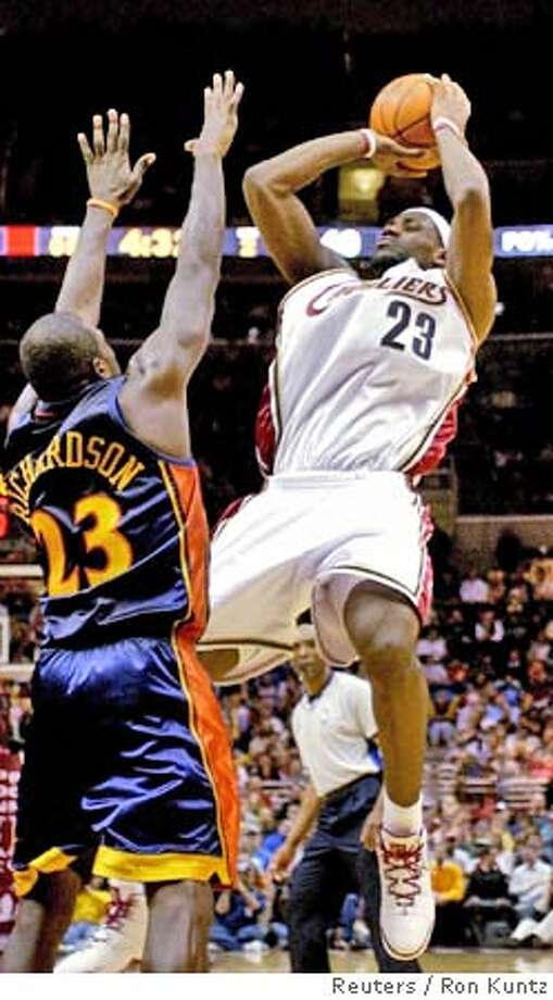 LeBron James (23) of the Cleveland Cavaliers makes a jump shot over Jason Richardson of the Golden State Warriors during the first quarter of their NBA game at The Q in Cleveland, Ohio February 11, 2006. REUTERS/Ron Kuntz 0 Photo: RON KUNTZ