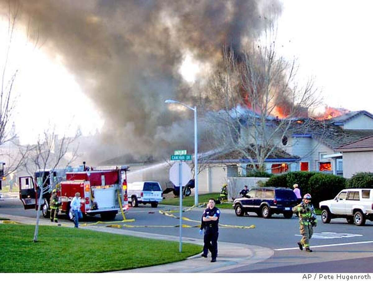 Smoke and flames rise from a home struck by a single engine plane in Roseville, Calif., Sunday, Feb. 12, 2006. The pilot of the plane was killed in the crash. (AP Photo/Pete Hugenroth)