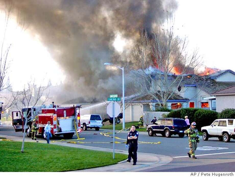 Smoke and flames rise from a home struck by a single engine plane in Roseville, Calif., Sunday, Feb. 12, 2006. The pilot of the plane was killed in the crash. (AP Photo/Pete Hugenroth) Photo: PETE HUGENROTH