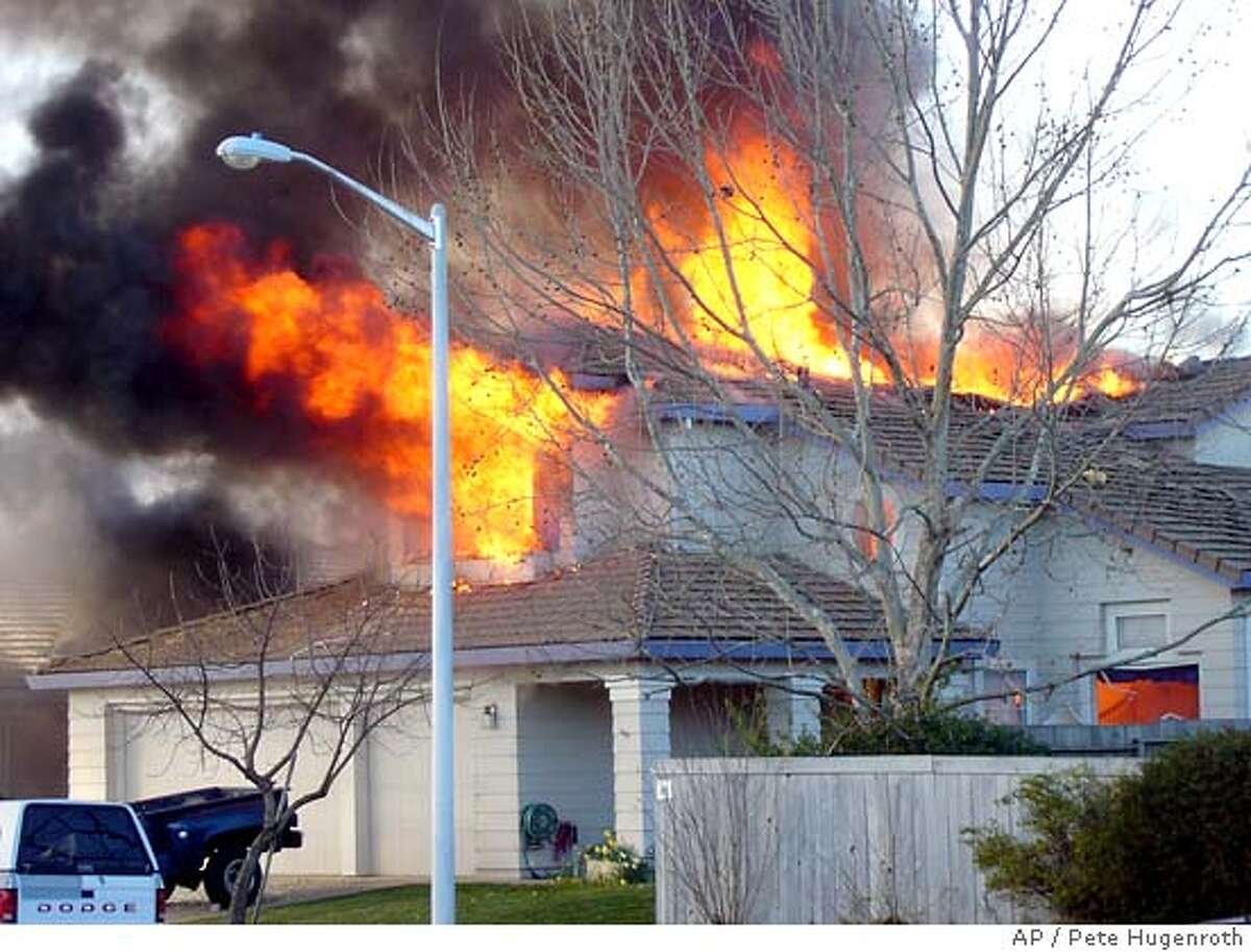 Flames pour from the second floor window of a home struck by a single engine plane in Roseville, Calif., Sunday, Feb. 12, 2006. The crash killed the pilot, according to the Federal Aviation Administration and local police. But there were conflicting reports about whether there were other fatalities or if the home was occupied at the time. (AP Photo/Pete Hugenroth)