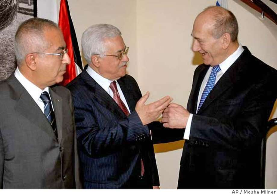 In this photo made available by the Government Press Office, Israeli Prime Minister Ehud Olmert, right, stands with Palestinian President Mahmoud Abbas, center, at the Prime Minister's Office in Jerusalem, Monday, Sept. 10, 2007. Israeli Prime Minister Ehud Olmert and Palestinian President Mahmoud Abbas sat down together on Monday to try to work out guidelines for resuming peace negotiation. Standing left is Palestinian Prime Minister Salam Fayyad. (AP Photo/GPO, Moshe Milner, HO) ** ISRAEL OUT ** ISRAEL OUT GPO HANDOUT PHOTO Photo: MOSHE MILNER