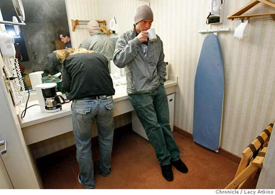 Tyler Smith sips his morning coffee at the Comfort Inn as his brothers girlfriend, Paige Nutt brushes her teeth before they leave for the Mavericks competition, Tuesday Feb.7, 2006, ih Half Moon Bay. The Mavericks competition, Tuesday Feb. 7, 2006, in Half Moon Bay. Winner Grant Baker of South Africa second place Tyler Smith. A look at the Mavericks surf competition through the eyes of surfer Tyler Smith of Santa Cruz, Feb. 6, 2006.  Photographer: Atkins, Lacy MANDATORY CREDIT FOR PHOTOG AND SF CHRONICLE/ -MAGS OUT Photo: LACY ATKINS