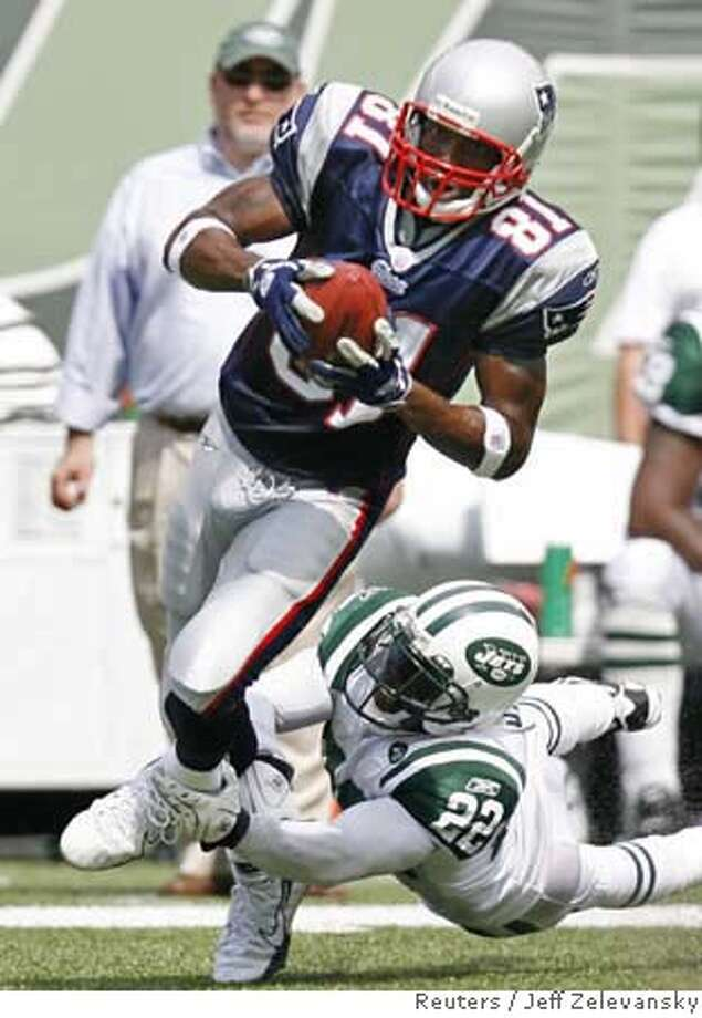 New England Patriots' Randy Moss (L) runs for a first down against the New York Jets as Jets defender Justin Miller (22) dives for the tackle during the first quarter of their NFL football game in East Rutherford, New Jersey, September 9, 2007. REUTERS/Jeff Zelevansky (UNITED STATES) Photo: JEFF ZELEVANSKY