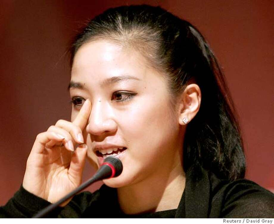 Figure skater Michelle Kwan of the U.S. wipes a tear from her eye during a media conference after pulling out of the Torino 2006 Winter Olympic Games in Turin, Italy, February 12, 2006. Kwan, a five-times world champion, sustained a groin strain during practice on Saturday. REUTERS/David Gray Photo: DAVID GRAY