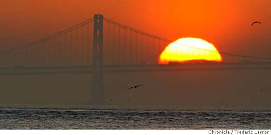 {object name} The morning commuters got a great view of the sun rising over the eastbay hills where the sun for a moment viewed from Fort Baker was resting Bay Bridge span. Today weather forecast is more of the same warm weather through the weekend. Shot at sunrise close to the waters edge at Fort Bakers Coast Guard station (north side under the Golden Gate Bridge) with a Canon EOS-1D Mark II N, lens (mm): 700, ISO: 320, aperture: 16, shutter: 1/320, exp. comp.: -0.3 set on shutter priority.  2/11/06  Frederic Larson Photo: Frederic Larson