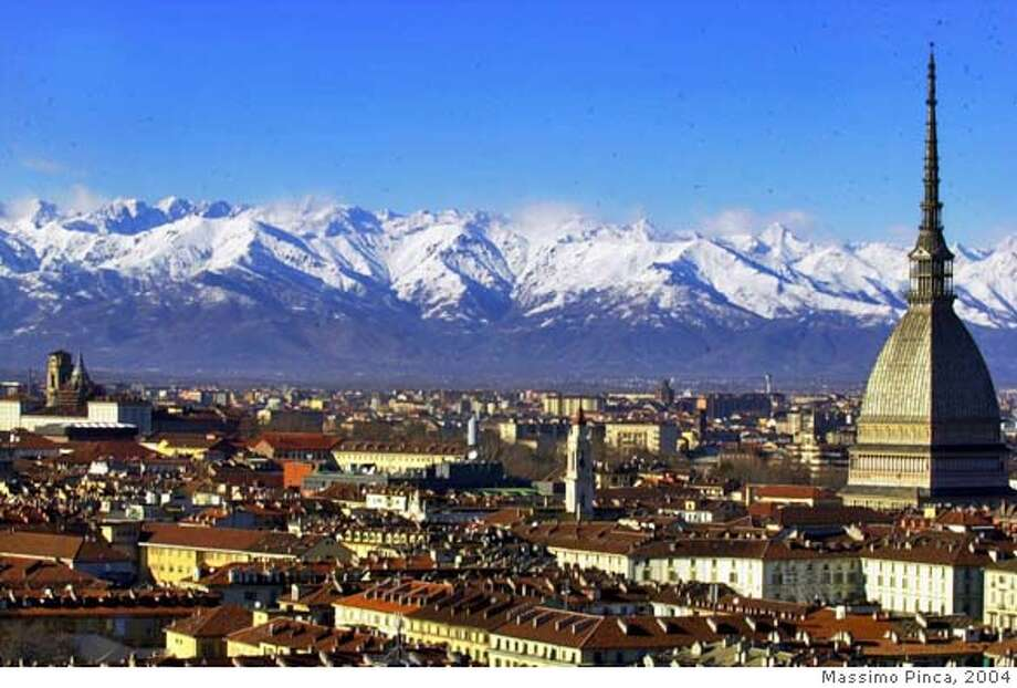 ** FOR USE AS DESIRED WITH 2006 TURIN WINTER OLYMPIC STORIES ** FILE ** A view of Turin, Italy, with the main city landmark, the Mole Antonelliana, at right, and the Alps in background are seen in this December 2005 photo. One million people is expected to visit Turin during the 2006 Winter Games. Many other tourists are expected to visit the city, completely remodeled on the occasion, and enjoy its world-class food and wines, after the Feb. 10-26 Olympics. (AP Photo/Massimo Pinca) A DEC. 2005 FILE PHOTO ** FOR USE AS DESIRED WITH 2006 TURIN WINTER OLYMPIC STORIES ** Photo: MASSIMO PINCA