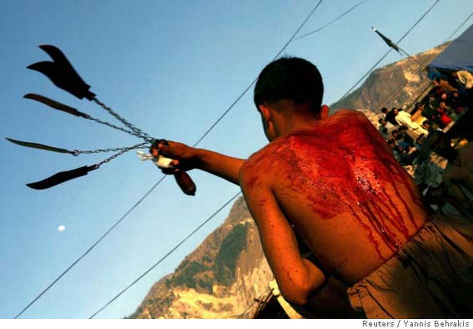 Kashmiri Shias flagellate them selfs with knifes attached to chains during an Ashura procession in the earthquake devastated city of Muzaffarabad in Pakistan-administered Kashmir February 9, 2006. A suspected suicide bombing on minority Shi'ite Muslims in Pakistan killed at least 23 people, wounded dozens and triggered violence on an important holy day that killed at least four more, police said. The attack targeted a procession in the town of Hangu in North West Frontier Province to mark Ashura, the holiest day for Shi'ites. Officials reported several blasts. REUTERS/Yannis BehrakisRan on: 02-10-2006  Shiites flagellate themselves with knifes attached to chains during an Ashura procession in the earthquake devastated city of Muzaffarabad in Pakistan-administered Kashmir. Ashura is the holiest day for Shiites. Photo: YANNIS BEHRAKIS