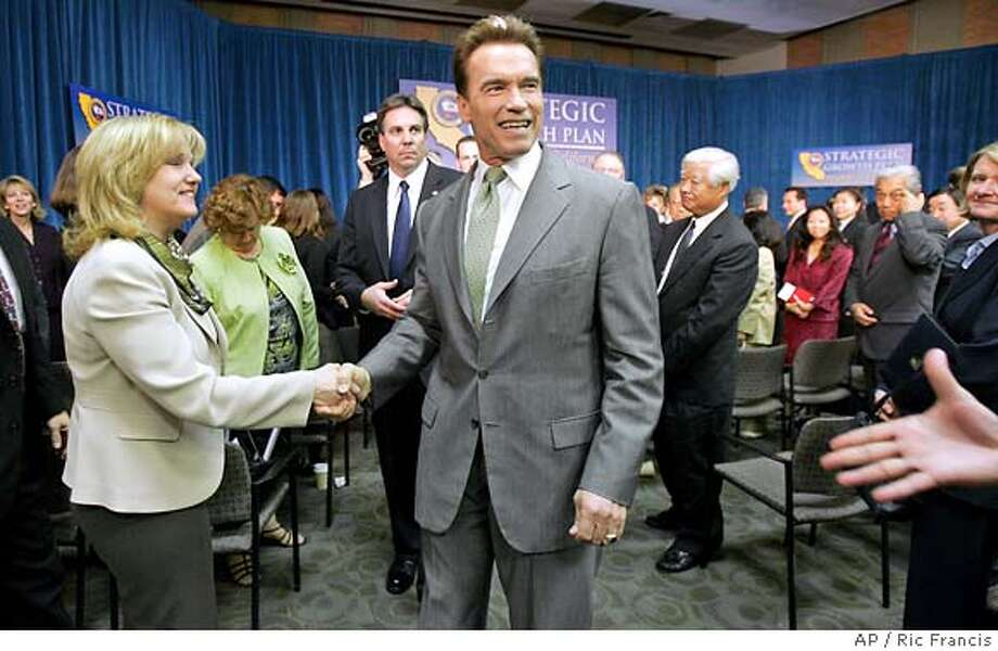 California Gov. Arnold Schwarzenegger departs after addressing a group of community and business leaders Tuesday, Feb. 7, 2006, at the University of Southern California in Los Angeles. Schwarzenegger spoke of his strategic growth plan for California. (AP Photo/Ric Francis) WOMAN AT LEFT IS UNIDENTIFIED. Photo: RIC FRANCIS