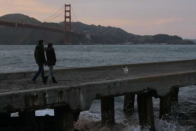 A couple walks at the Marina in San Francisco during a break in the wet winter storm passing through the Bay Area on Saturday, March 17, 2012. Photo: Erik Verduzco, The Chronicle