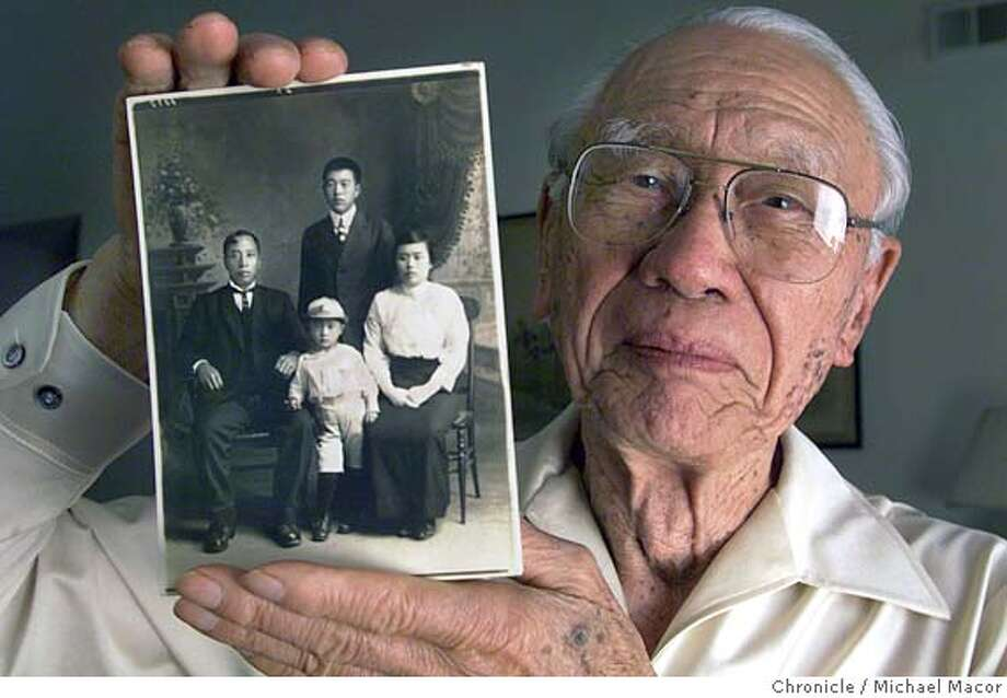 """SHIKANO 1-C-19APR99-SC-MAC """"Voices of the Century"""" series. 87 year old Kazuo Shikano of Pleasanton holds a photograph of himself with his cousin and parents. Shikano 3 or 4 years old in picture with his father Ichizo, (left) mom Ichi, (right) and cousin Mori (top). Shikano spent time in the Topaz, Utah relacation camp and was also a farmer in the Fremont area. by Michael Macor/The Chronicle CAT"""