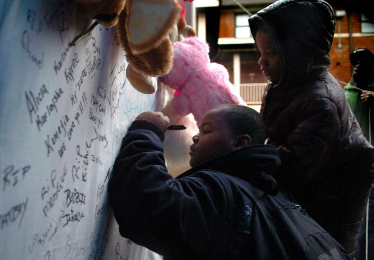 Ten-year-old Deontae Johnson adds a message to the memorial set up for Tiana Black and her four-year-old daughters Tyasija and Nyasija and five-year-old son Nyshon who died early Friday morning in a fire in their unit at the P.T. Barnum Apartments public housing complex in Bridgeport.