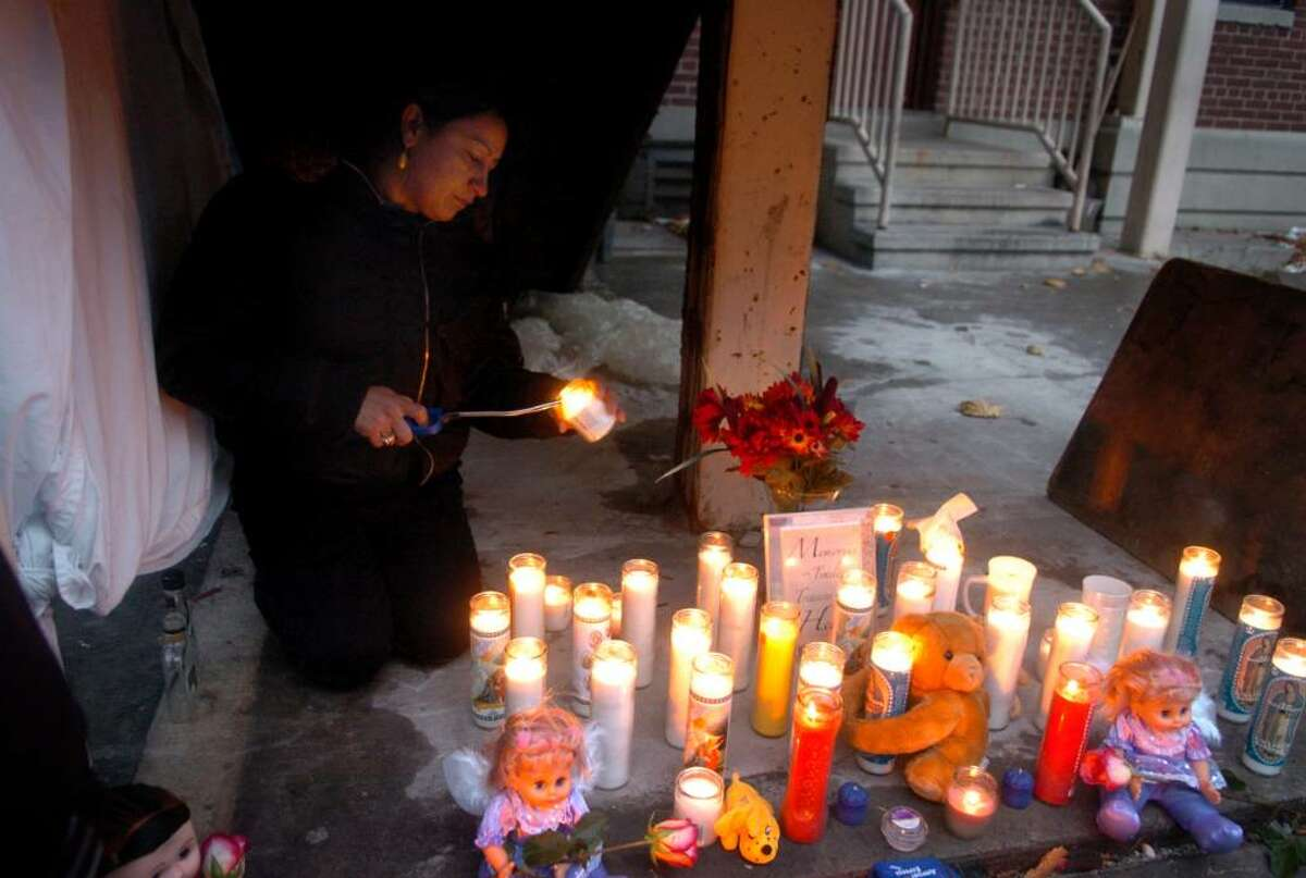 Lillian Caraballo lights a candle in memory of her good friend Tiana Black Friday afternoon outside Black's apartment where a memorial has been set up for Black and her three children who died early Friday morning in a fire in their unit at the P.T. Barnum Apartments public housing complex in Bridgeport.