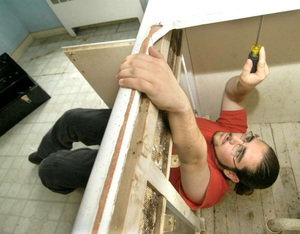 Frank Sutton, 16, works under a kitchen countertop Tuesday at 3 Mill Ridge Rd. in Danbury. Abbott Tech students from the heating and plumbing department are getting hands-on training doing work for the Danbury Housing Authority.