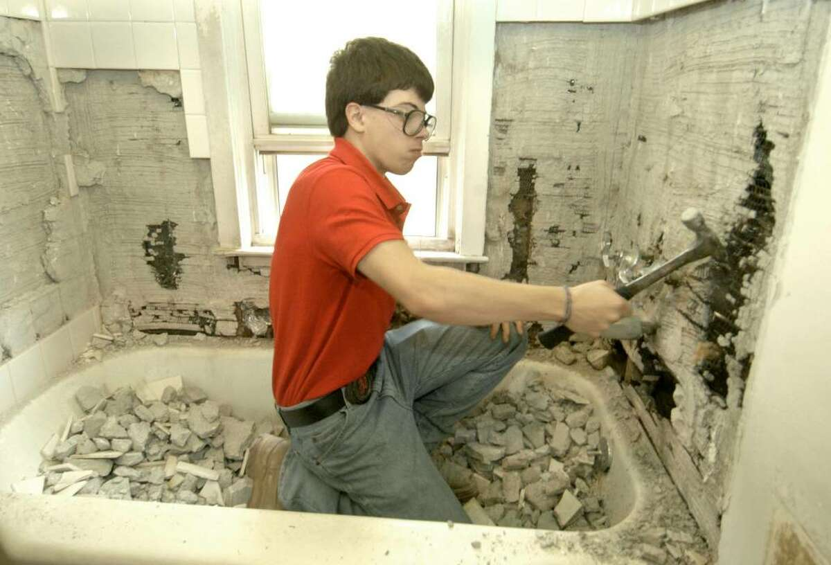 Trevor Masse, 16, tears apart the tiles over a bathroom tub where students from Abbott Tech are preparing to do plumbing in a home owned by the Danbury Housing authority Tuesday, November 10, 2009