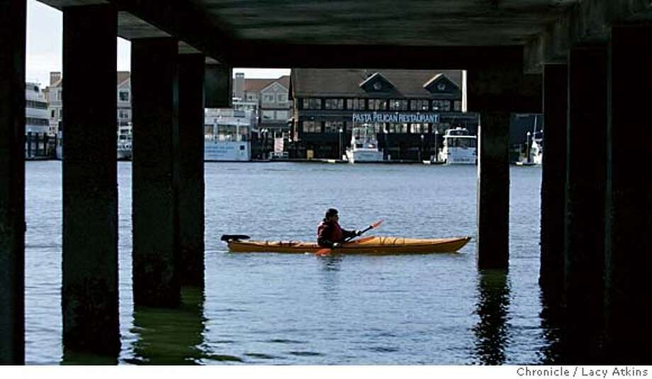 """A student of the Calforina Canoe&Kayak shop paddles down the estuary in the bay Sunday Febl. 5, 2006. I'm doing feature on Calfornia Canoe & Kayak shop in Jack London Square. They've been there 13 years, but their lease is up, a new commercial landlord is trying to squeeze them for more dough, and they may need to find a new waterfront location... somewhere in the Bay Area. Story will look at their fate as a subset of how development takes place around the Bay, and how much of a place there is for public access and a """"mom-and-pop"""" shop like this. On Sunday, there's a """"kayak basics"""" class that starts at 10 a.m.... a real introduction to beginners. The students will get on the water between 10:30 and 11 a.m.. We'd like pix of that class to go with the story - land shots of the class cd be OK if they help establish Jack London Square location; photo of the mom& Pop in question Keith Miller and his wife Tammy, and maybe a photo of the shop front that puts it in the context of Jack London Square and its commerce and clientele.Feb. 5, 2006.  Photographer: Atkins, Lacy MANDATORY CREDIT FOR PHOTOG AND SF CHRONICLE/ -MAGS OUT Photo: LACY ATKINS"""