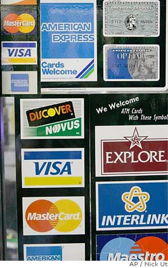 Credit card decals adorn a store window in the Hollywood section of Los Angeles, Wednesday, Sept. 5, 2007. Consumers will soon be seeing changes in credit card terms, and in other loans, due to the turmoil in the mortgage market. (AP Photo/Nick Ut) Photo: Nick Ut