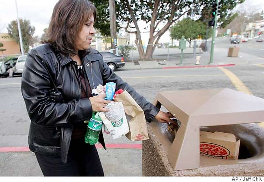 ** ADVANCE FOR MONDAY, FEB. 6 ** Oakland Tech high school principal Sheilagh Andujar puts litter she picked up from the sidewalk into a trash can outside the high school in Oakland, Calif., Thursday, Jan. 26, 2006. The Oakland City Council is considering the nation's first fast-food litter tax to pay for cleanup crews. (AP Photo/Jeff Chiu) Photo: JEFF CHIU