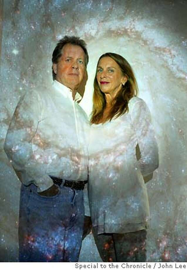 FERRIS_03_JOHNLEE.JPG  GLEN ELLEN, CALIF - AUG 31: Science writer Timothy Ferris (cq), left, with his wife Carolyn Zecca Ferris (cq), standing in front of a projection of the Whirlpool Galaxy, inside Ferris' Rocky Hill Observatory near Glen Ellen, California. By JOHN LEE/ Photo: John Lee