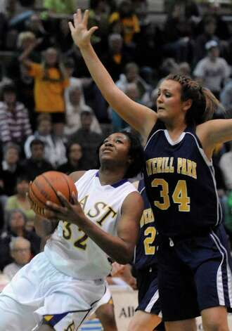 East's Tyra Jones (32) looks to shoot from under the arm of Averill Park's Bridget Carney (34) in the state girls' Class A basketball final in Troy, N.Y. on Saturday, March 17, 2012. (AP Photo/Tim Roske) Photo: Tim Roske