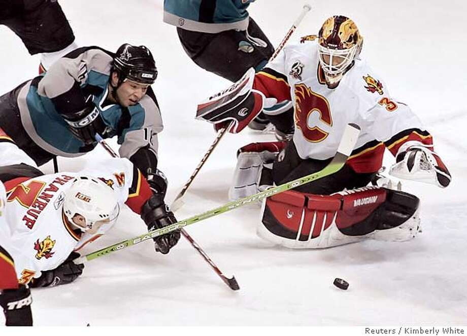 Calgary Flames goaltender Miikka Kiprusoff (R) stops a shot by San Jose Sharks' Mark Smith (C) as Flames' Dion Phaneuf defends in the first period of a NHL game in San Jose, California, February 6, 2006. REUTERS/Kimberly White Photo: KIMBERLY WHITE
