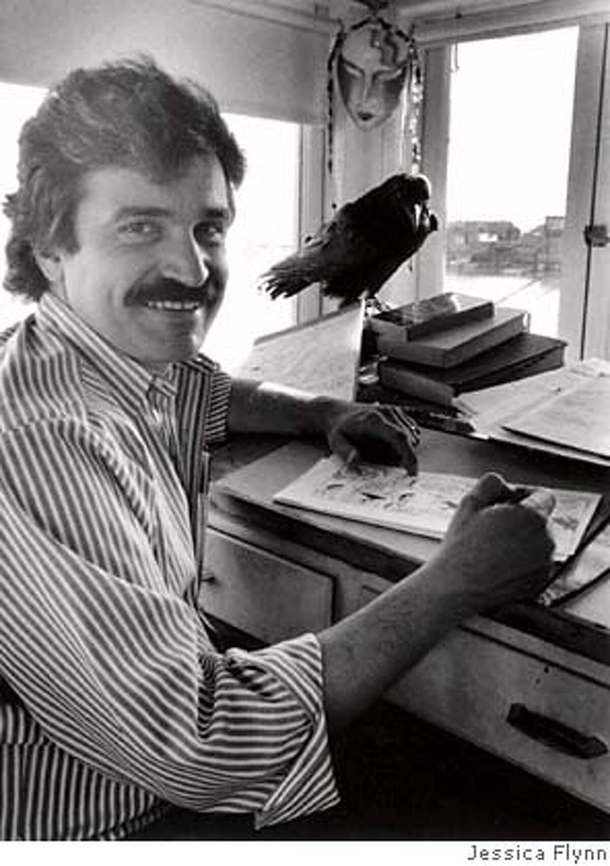 """Phil Frank, San Francisco Chronicle cartoonist, works on his comic strip """"Farley"""" in his studio aboard an 1888 ferry boat in Sausalito, CA. Bruce the raven looks on."""