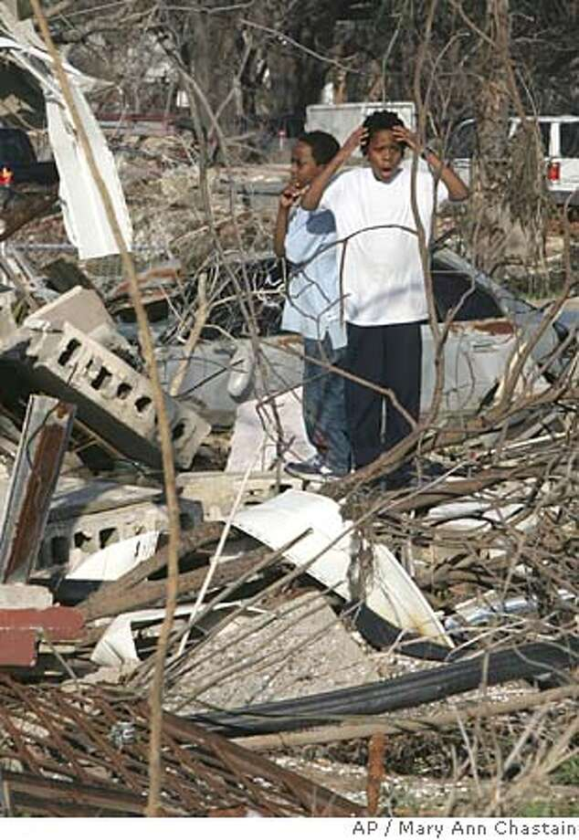 Brice Nolan, 11, reacts after looking at the remains of his house in the lower 9th ward section of New Orleans, as his friend, Darrell Bumfield, 8, looks on Friday, Feb. 3, 2006. This was the first time the boys have been back to their community to see the destruction since Hurricane Katrina hit last year. (AP Photo/Mary Ann Chastain) Photo: MARY ANN CHASTAIN