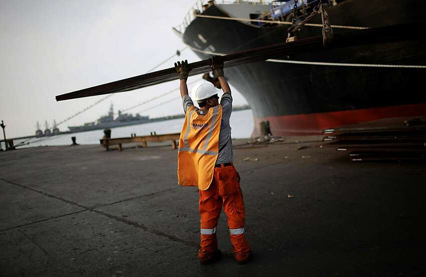 A dock worker unloads a steel sheet at the APM Terminals BV area of the Port of Callao in Lima, Peru, on Thursday, March 15, 2012. Economic activity in Peru expanded 5.4 percent from a year earlier, compared with 6 percent growth in December, the government's statistics agency said today in an e-mailed report. Photographer: Dado Galdieri/Bloomberg