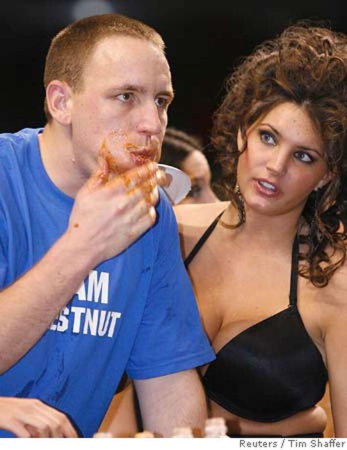 "Wingbowl participant Joey Chestnut (L) holds back a mouthful of wings as a ""Wingette"" looks on during the 14th annual Wingbowl event in Philadelphia, February 3, 2006. Chestnut from San Jose, California ate 173 wings to take the crown. REUTERS/Tim Shaffer 0 Photo: TIM SHAFFER"