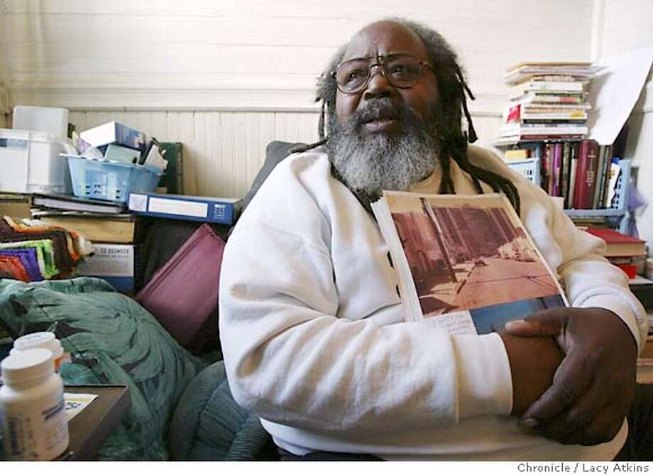 Elzie Byrd who was beaten up by officer John Haggett back in the 1990 while he and his family lived at the Genneva Towers, holds a picture of the Towers as he talk about his encounters, at his home in San Francisco, Jan. 20, 2004. Lacy Atkins / The Chronicle Photo: Lacy Atkins